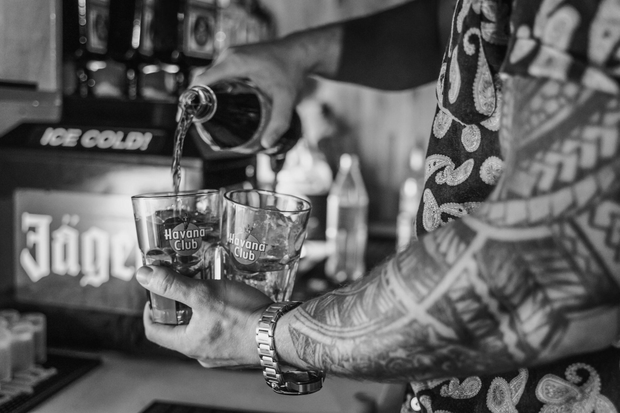 Barkeeper schenkt 2 Gläser mit Drinks aus der Rude7 Bar ein